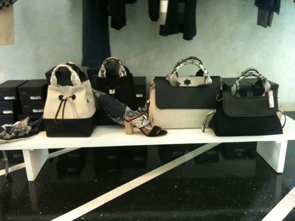 un tavolo di color bianco con delle borse di color nero e beige