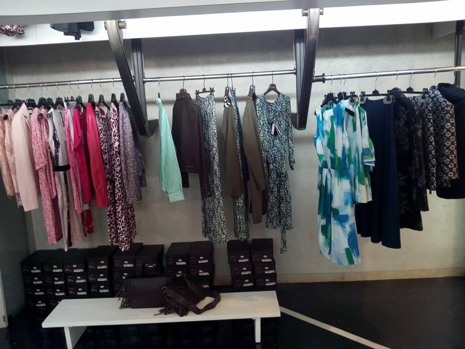 degli appendini con degli abiti di color rosa, azzurro e nero in un boutique
