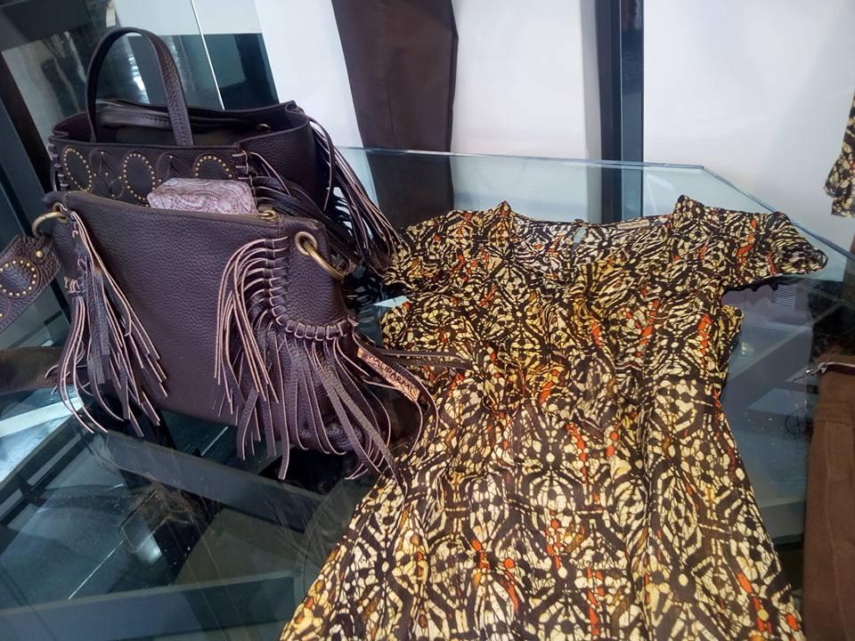 una borsa di pelle con le frangette e un abito accanto