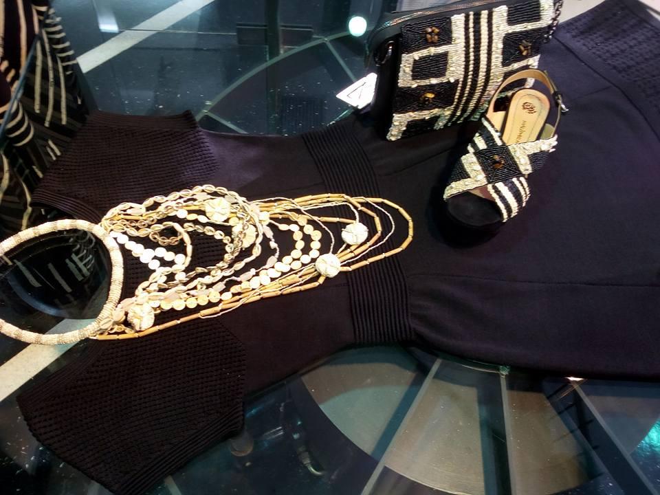 un abito di color marrone scuro e degli accessori dorati