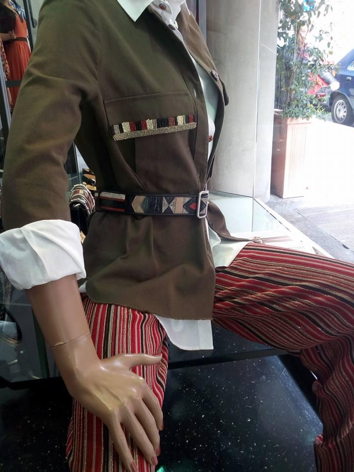 un manichino con dei pantaloni con righe di color nero e rosso e una giacca di color verde