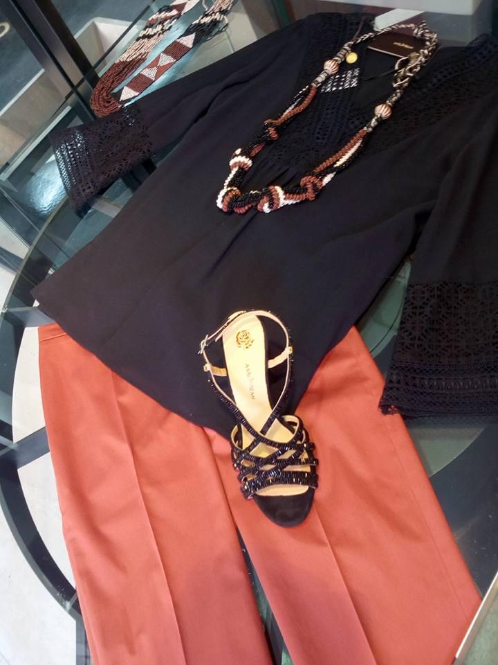 dei pantaloni di color arancione e una camicia di color nero