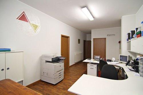 un ufficio con una scrivania bianca e una fotocopiatrice