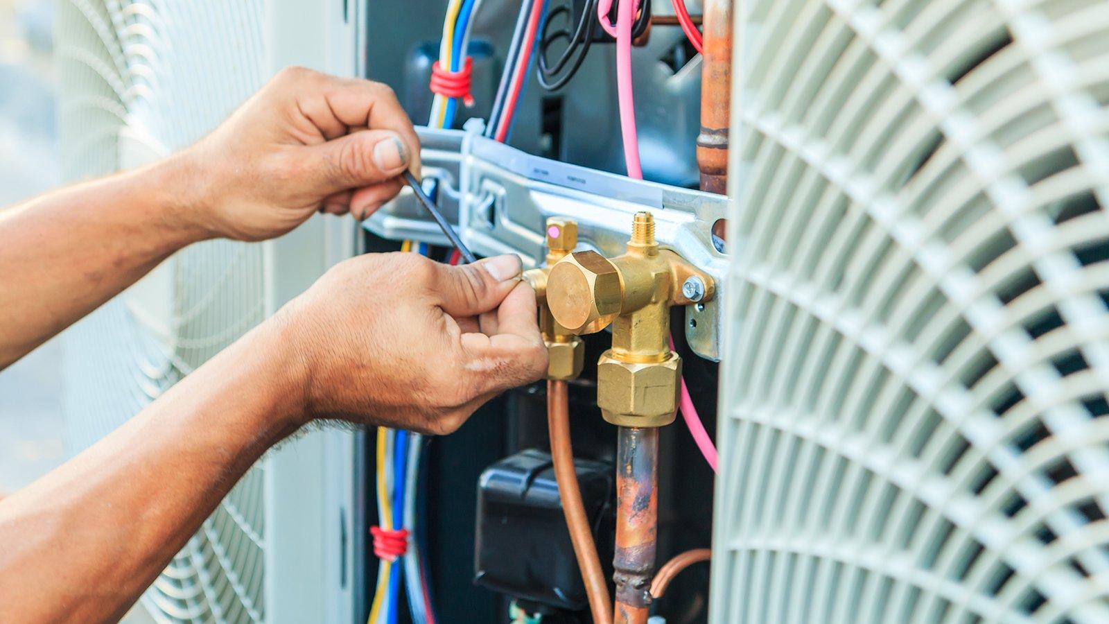 due mani con una chiave a brugola che avvitano un bullone vicino a una valvola dorata con dei tubi arancioni e dei fili elettrici a vista