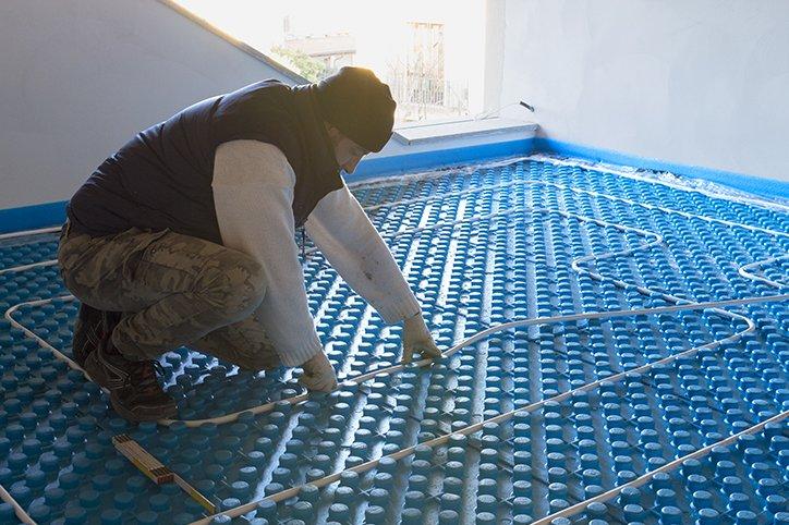 un idraulico che sta installando un sistema radiante sul pavimento
