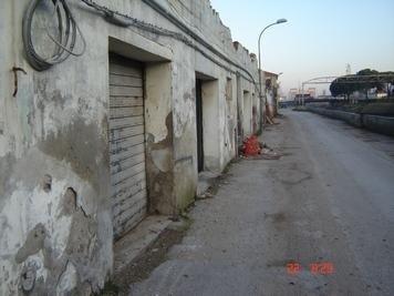 una strada e visto di una serranda in uno stabile