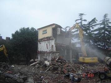 una demolitrice e le macerie di uno stabile