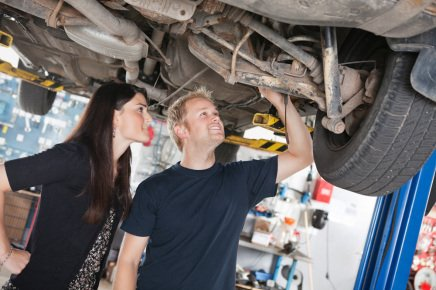 Mechanic and customer checking a car at a MOT centre