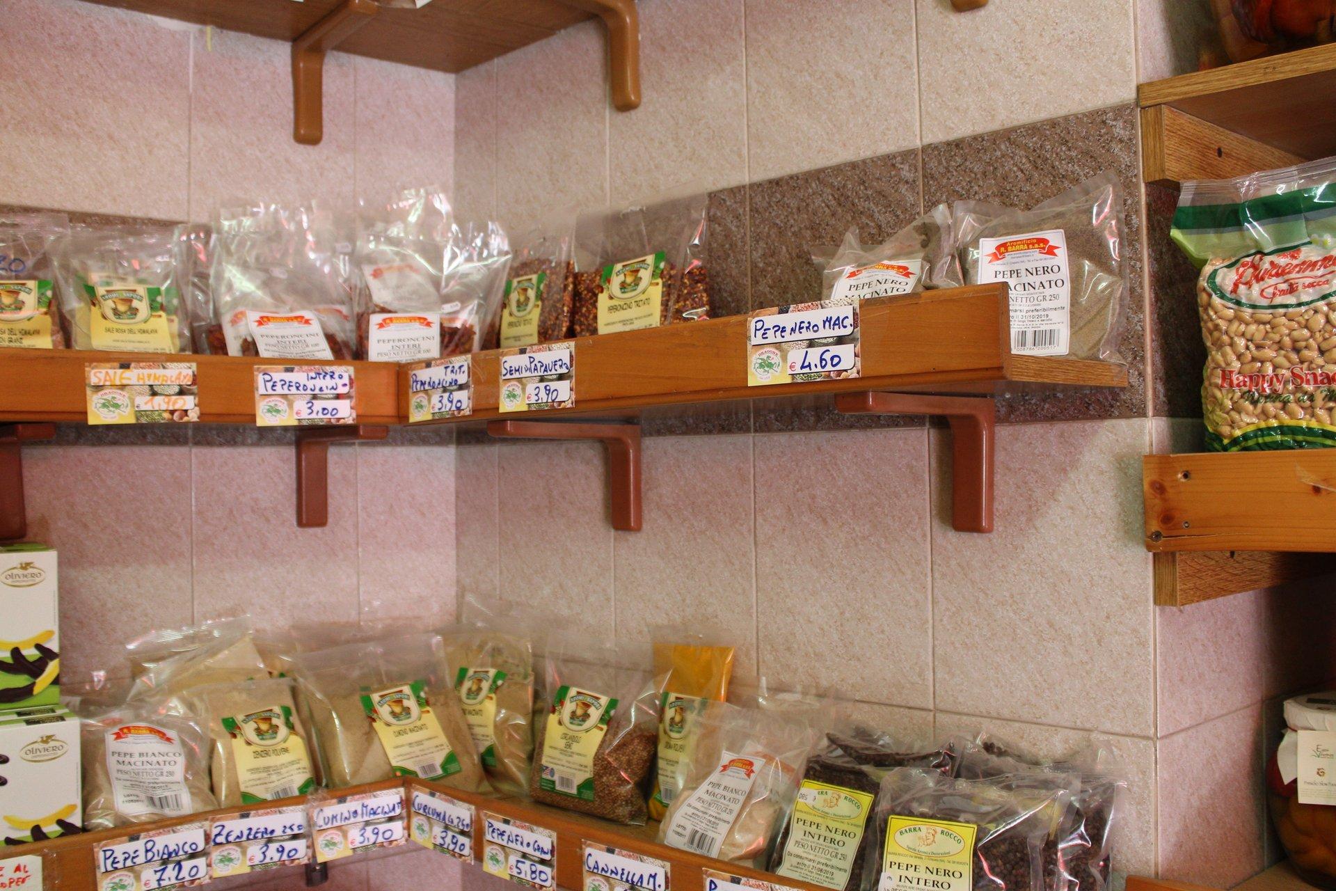 vari tipi di spezie e frutta secca negli scaffali del negozio
