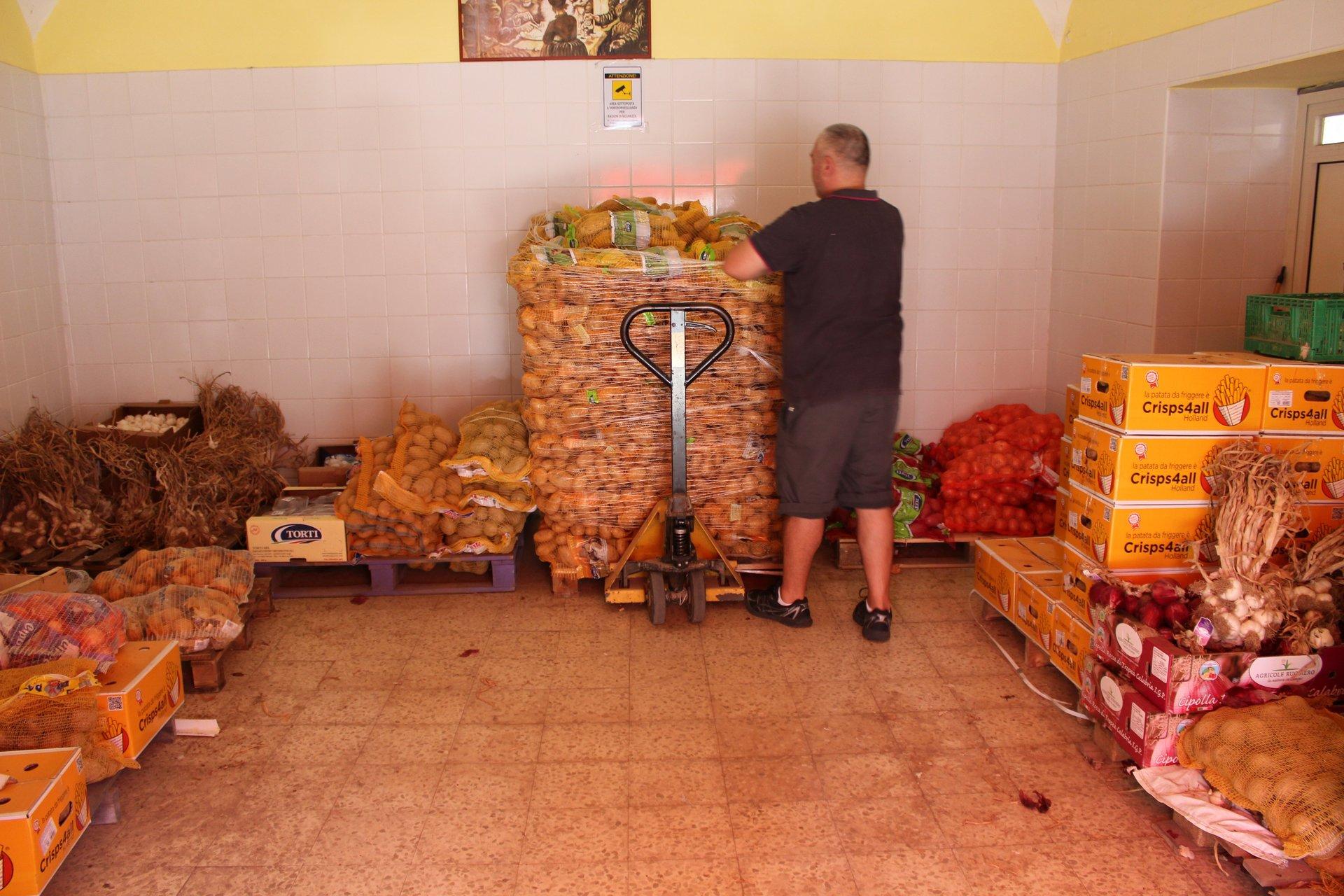 Uomo che lavora al carico-scarico di patate