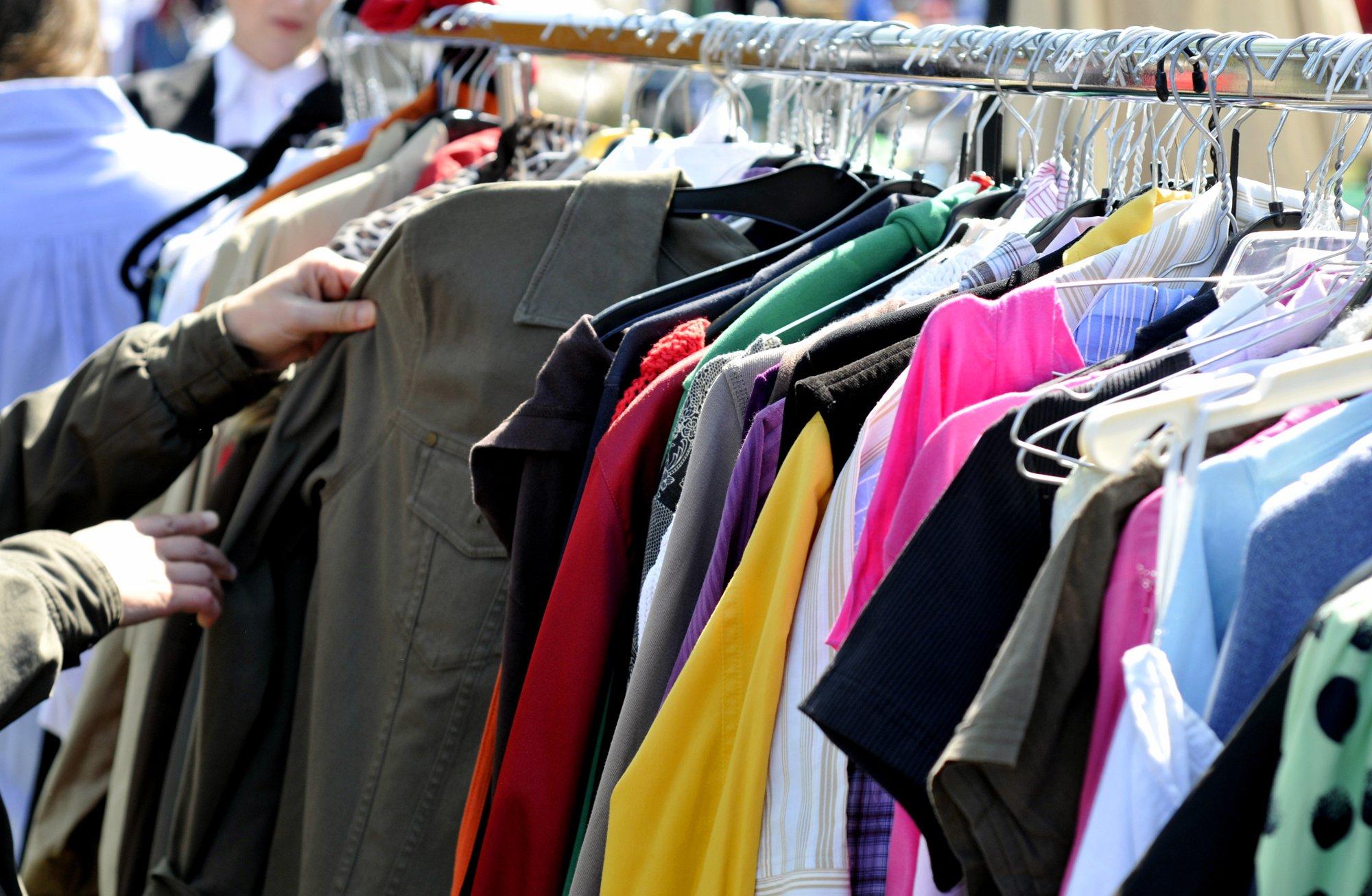 gente mentre controlla vestiti appesi su grucce in un negozio