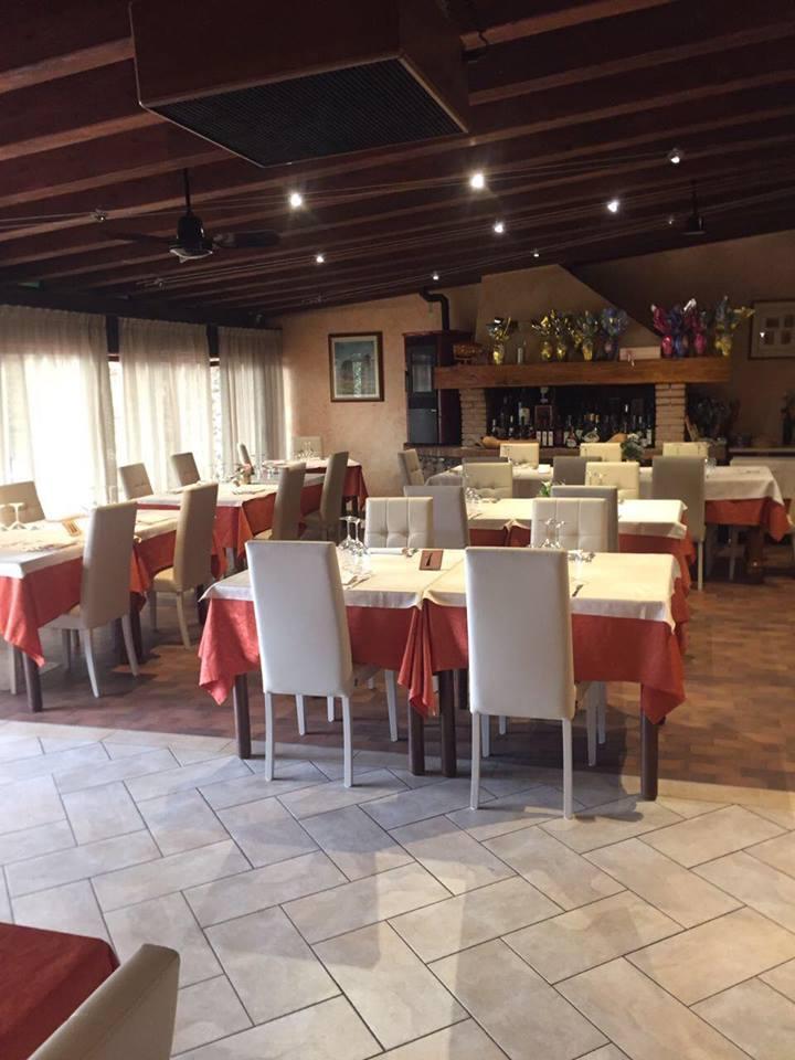 vista interna del ristorante con tavoli apparecchiati con soffitto in legno