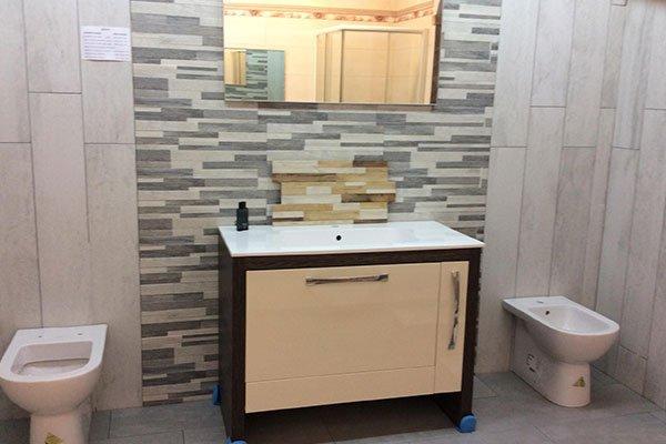 Bagno con pareti di marmo chiaro esclusa la zona di lavandino dove si combinano piccole lamelle di marmo di multiple bruni