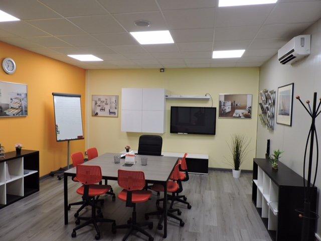 piccolo ufficio con tavolo rettangolare e sedie rosse