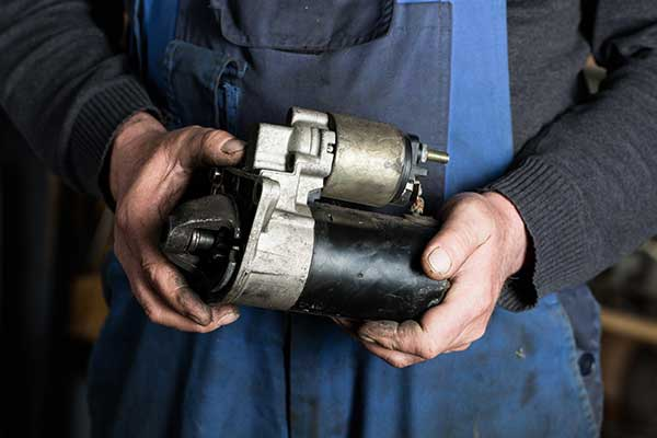Car mechanic holding car starter gear in Texarkana