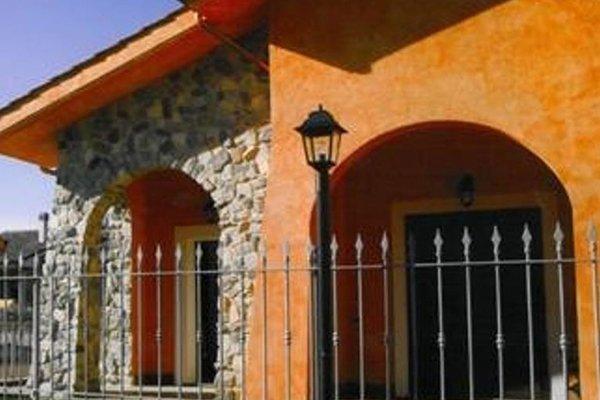 una ringhiera e una casa in pietra e di color arancione