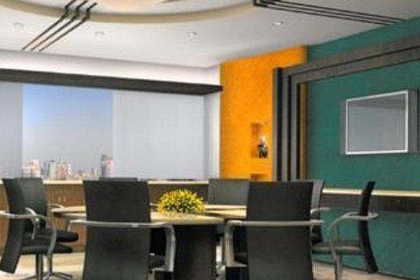 una sala conferenze con un tavolo, delle sedie e uno schermo