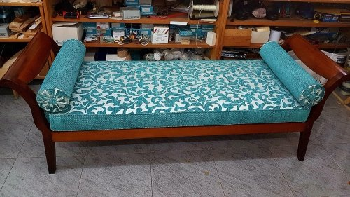 Un divano di legno rivestito in una stoffa di color azzurro