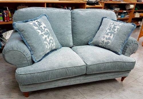 un divano di color azzurro con dei cuscini