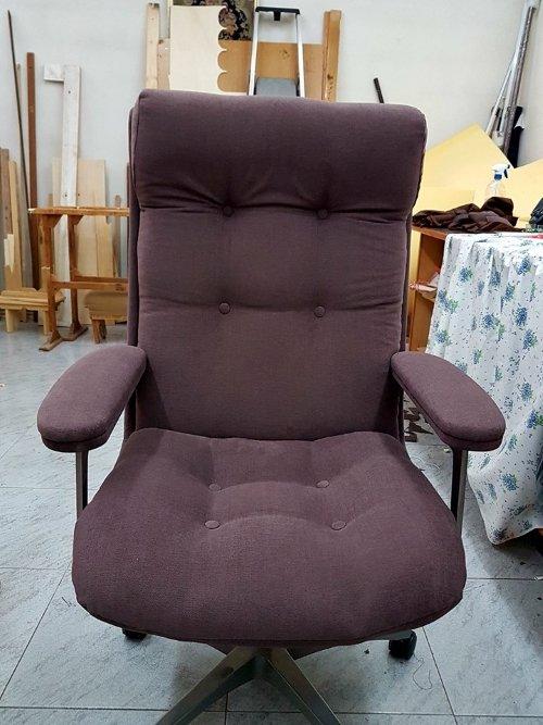 una poltrona di ufficio rivestita in una stoffa di color viola