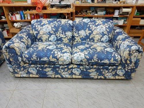 un divano rivestito in una stoffa di color blu con dei disegni a fiori