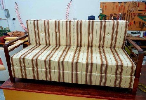un divano con una struttura in legno e dei cuscini imbottiti in stoffa di color beige con le righe di color marrone