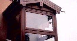 finestra con infissi in legno e tettoia