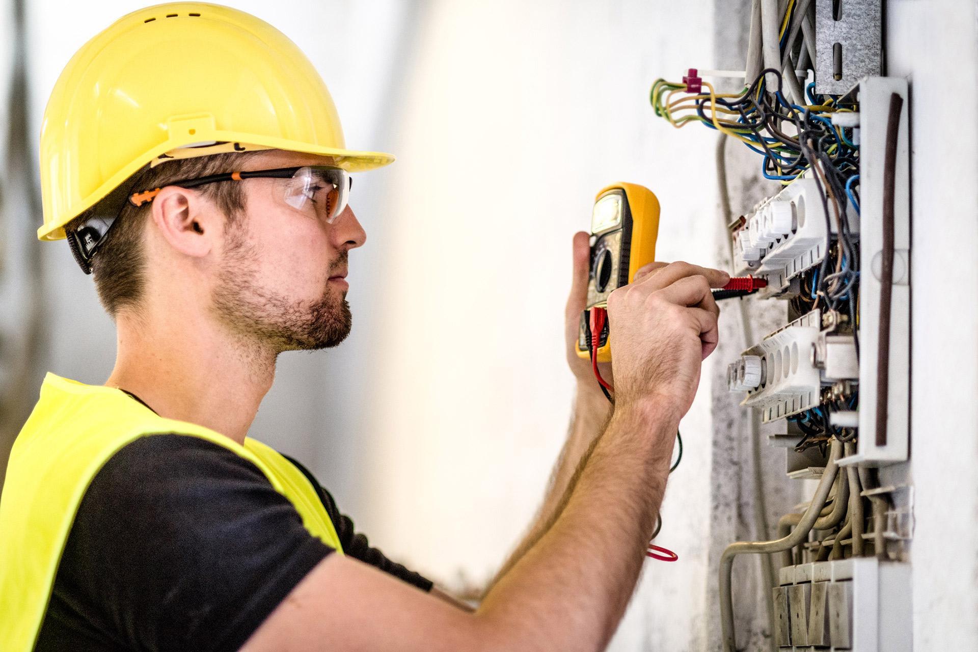 un tecnico con un tester davanti a un quadro elettrico