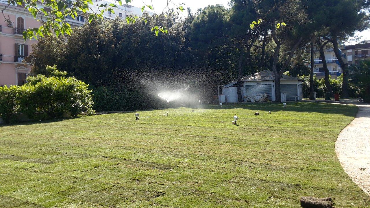 vista di un prato e di un impianto di irrigazione funzionante che sta spruzzando dell'acqua
