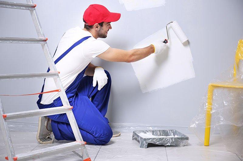 uomo che dipinge una parete