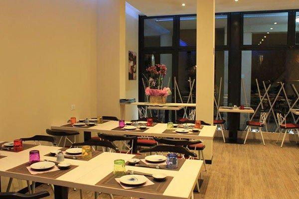 sala da pranzo di un ristorante con tavoli bianchi apparecchiati con tovagliette marroni e bicchieri colorati