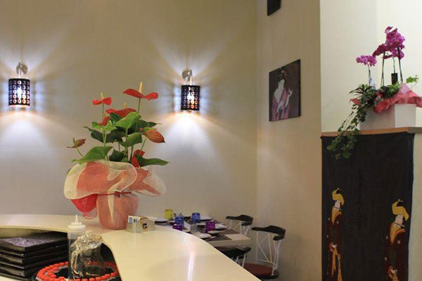 vista del bancone all'interno del ristorante con sopra un vaso di fiori rosa e dietro un altro mobile marrone con sopra un vaso di fiori