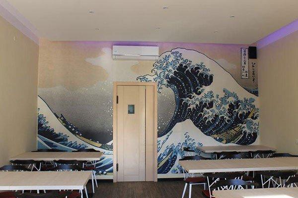 una sala con dei tavoli bianchi in fondo una porta di color beige e una parete dipinta raffigurante  un' onda e una barca che viene travolta