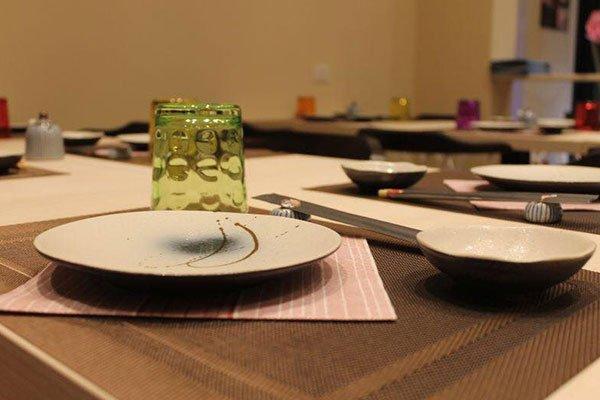 un piatto, una ciotola e un bicchiere di color verde  su una tovaglietta marrone