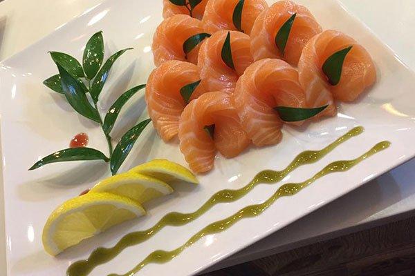 un piatto di sushi al salmone con tre fette di limone e una decorazione con delle foglie