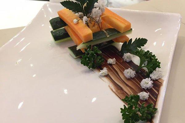 delle zucchine e delle carote tagliate a bastoncini gli uni sopra gli altri e accanto una decorazioni con fiori bianchi, foglie verdi e salsa di color marrone