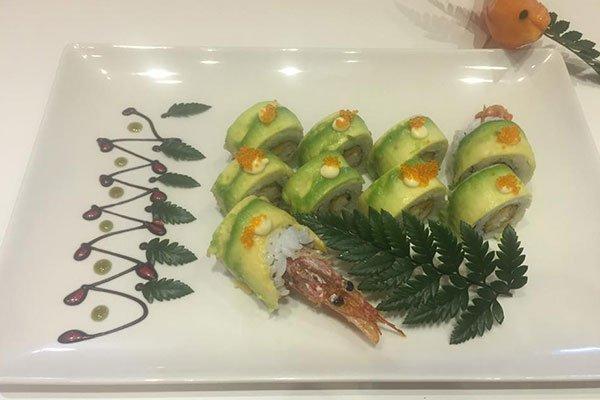 piatto a base di sushi con avocado, una testa di un gambero e foglie decorative