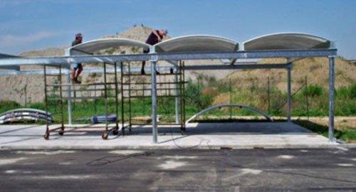 due uomini al lavoro su delle tettoie sorrette da una struttura di ferro