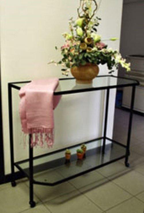 un tavolino in ferro battuto e vetro con sopra un vaso di fiori