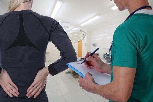 medico controlla paziente con mal di schiena