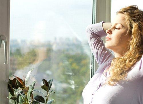 Woman standing near the window and enjoying the sun