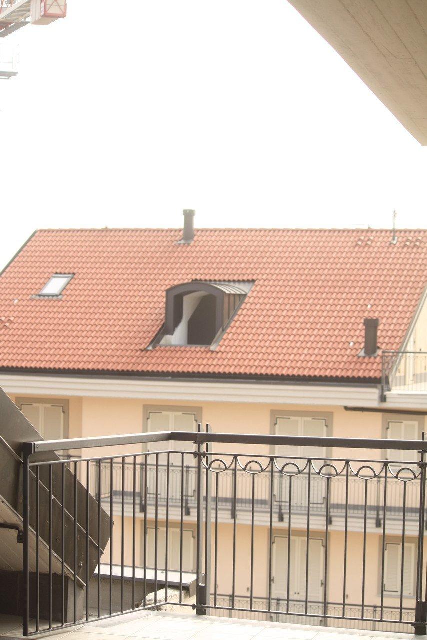 foto da un balcone con palazzina sullo sfondo