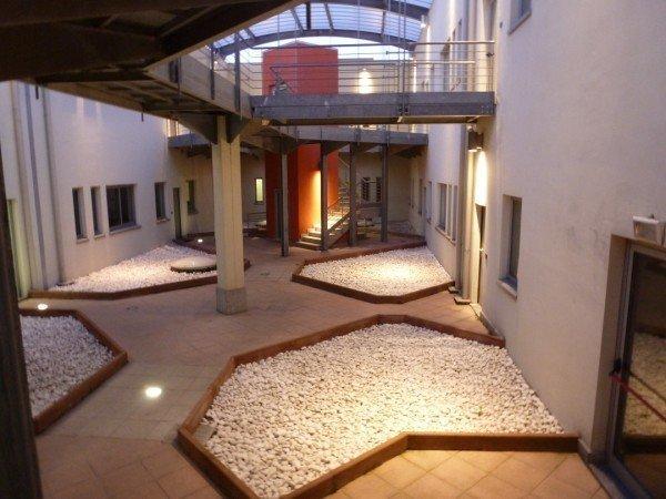 giardino condominiale con aiuole in sassi