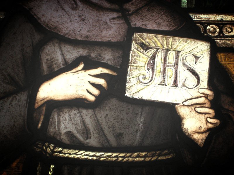 Stained glass image of St Bernardine and the IHS emblem