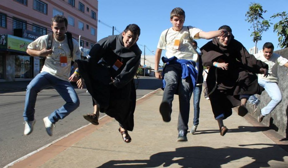 A streetscene of two young Friars and friends jumping in the air