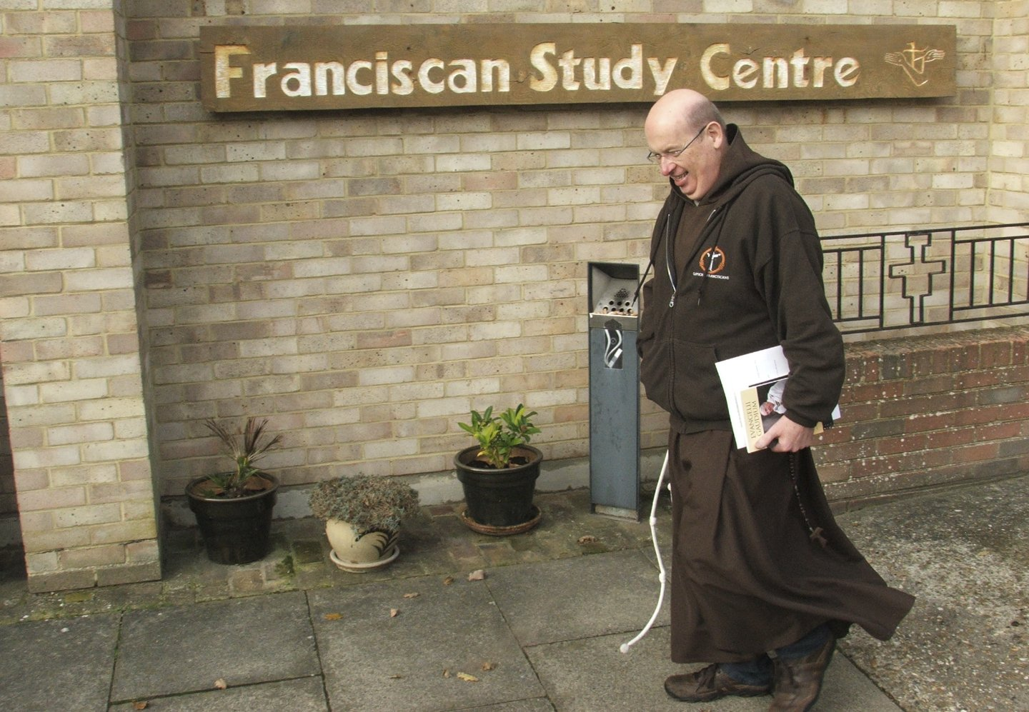 Friar walking in front of Study Centre library