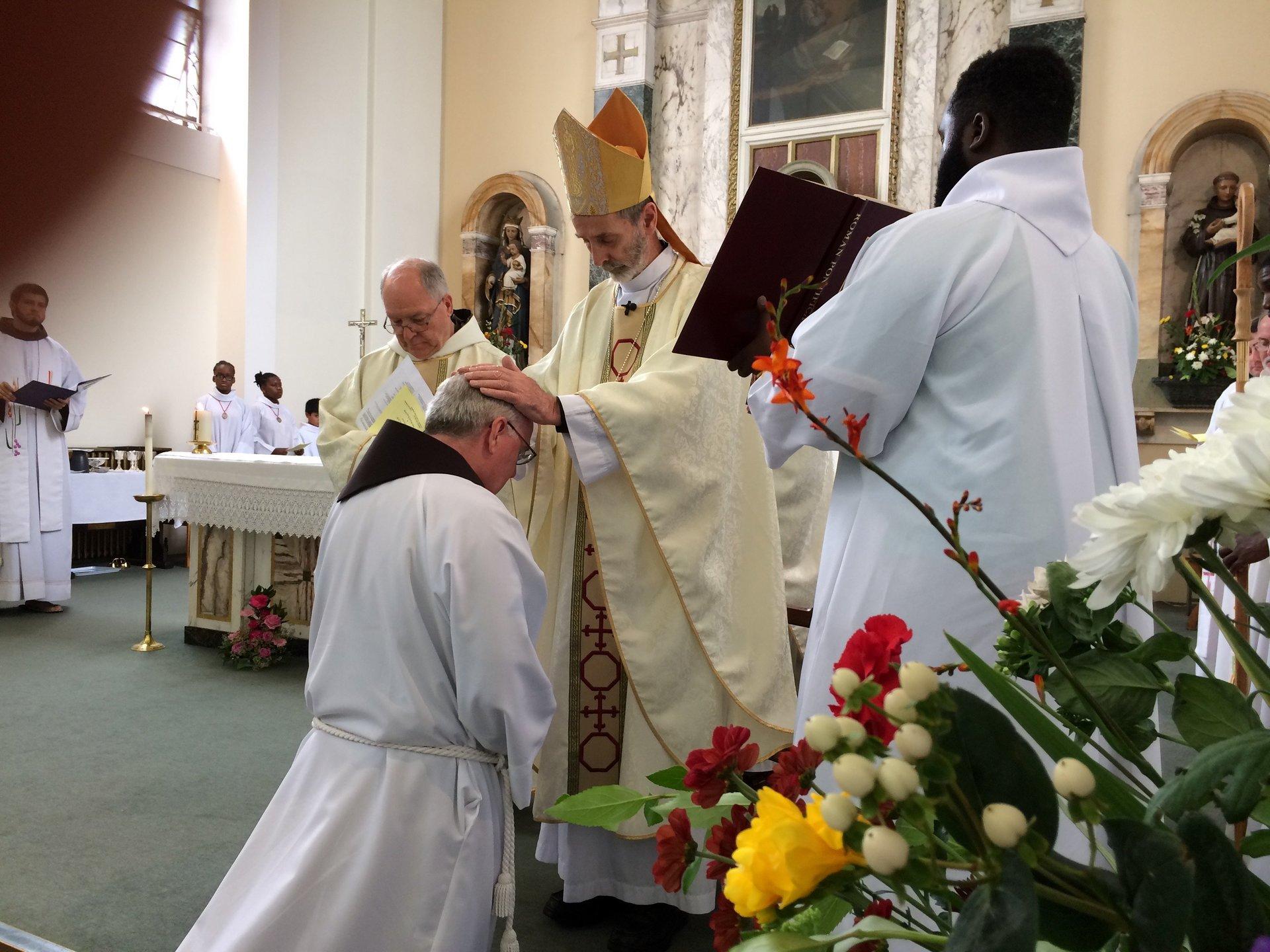 Bishop lays hands on his head
