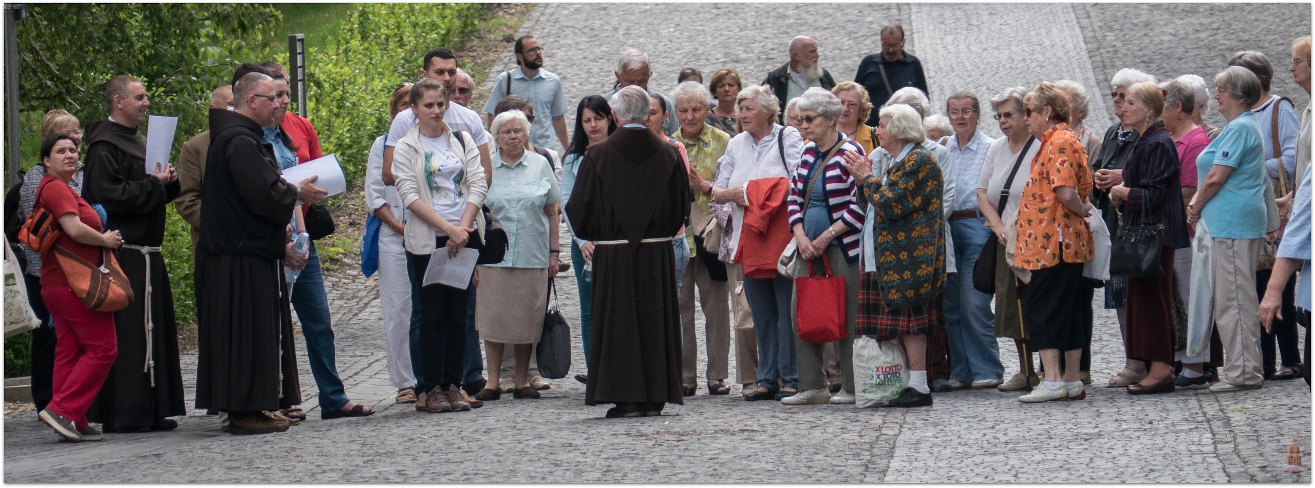 A streetscene of a Friar leading a group pf elderly pilgrims