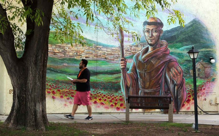 Street fresco of St Francis of Assisi with a man walking past