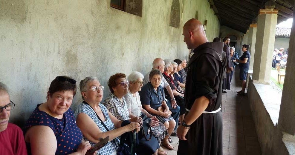 A Friar stands before a row of sitting pilgrims